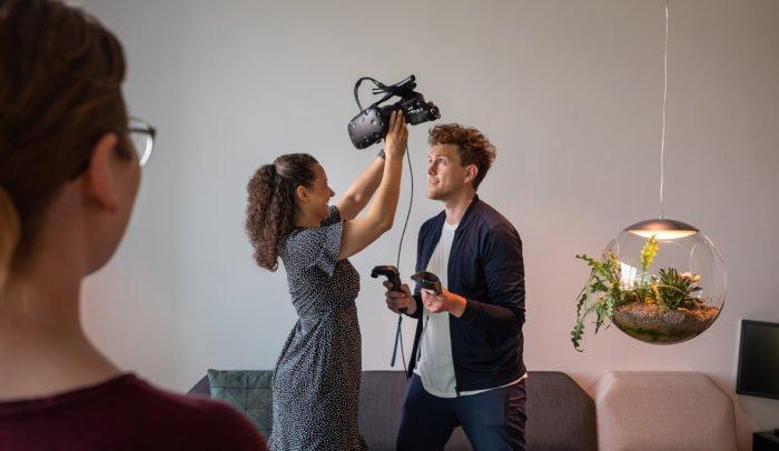 En person som hjälper en annan att sätta på ett VR-headset