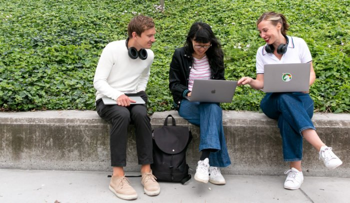 Tre personer som sitter och med bärbar dator utomhus