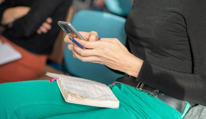 En person som sitter med sin mobiltelefon och ett anteckningsblock i knät