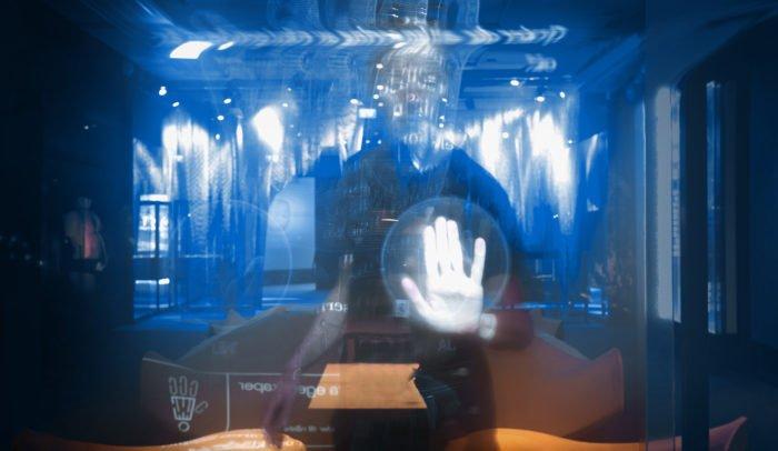 Siluett av en person som står bakom en pekskärm i en futuristisk miljö